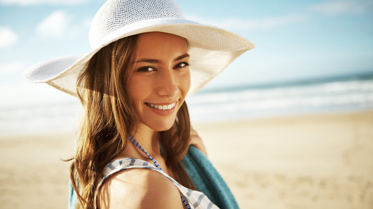 A young woman standing on the beach and enjoying the scenery and sunshine