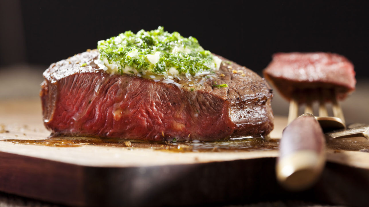Steak with green butter on wooden board