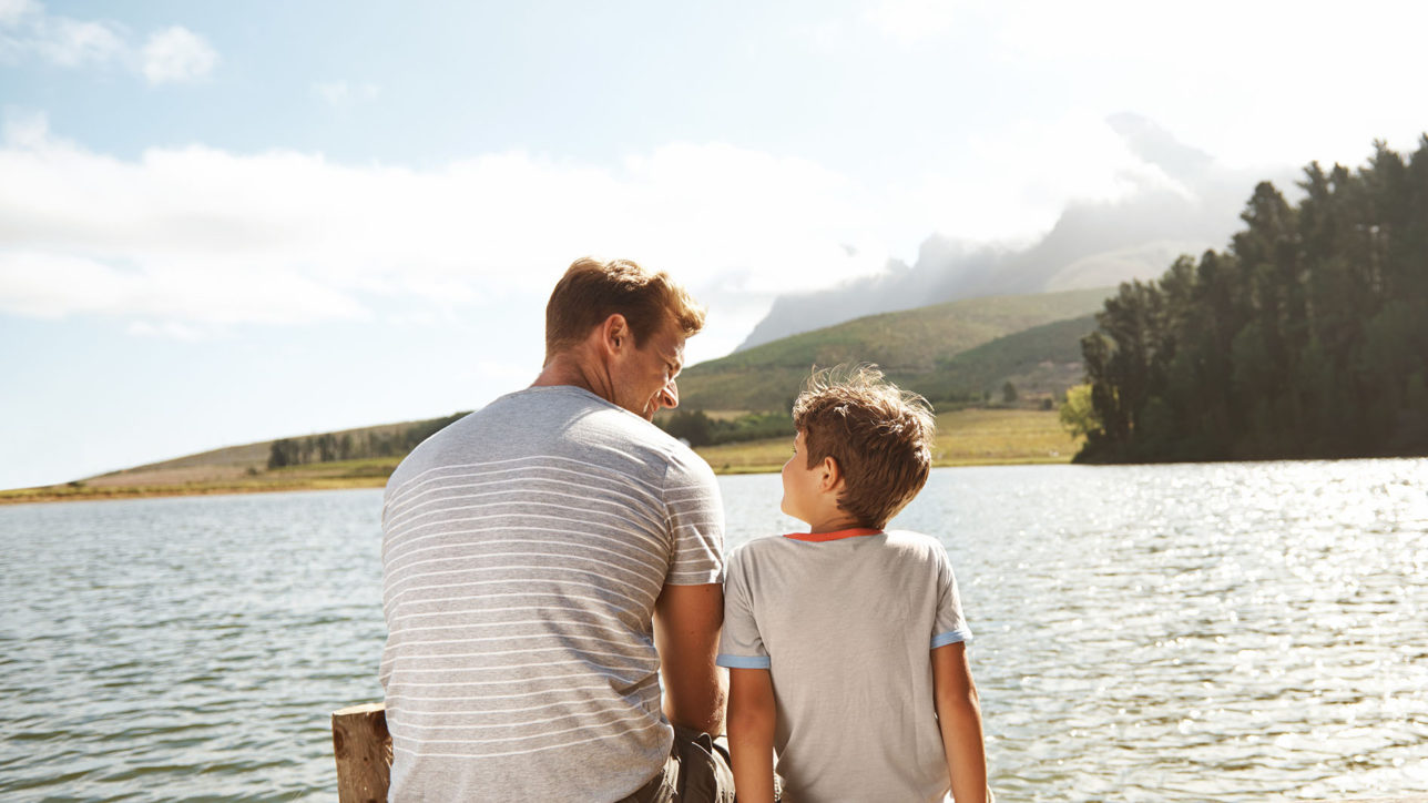 Rear view of a father and son bonding while they sit on a pier by a lake with copyspace